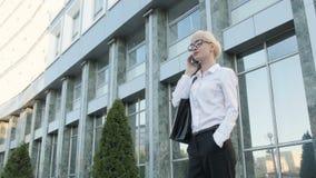 Menina loura da mulher de negócios nova bonita nos vidros que chama pelo telefone no centro de negócios do fundo Fotografia de Stock