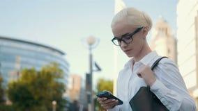 Menina loura da mulher de negócios nova bonita nos vidros que chama pelo telefone no centro de negócios do fundo Imagem de Stock