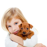 Menina loura das crianças com pinscher do filhote de cachorro do cão o mini Fotografia de Stock Royalty Free