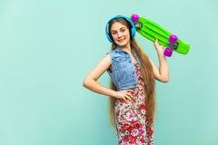 A menina loura de cabelos compridos bonita feliz no vestido e em fones de ouvido azuis, tendo o divertimento com o patim plástico Imagens de Stock