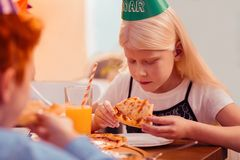 Menina loura de cabelos compridos concentrada que olha a parte de pizza imagem de stock royalty free