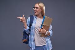 Menina loura de encantamento com documentos que aponta o dedo em algo interessante foto de stock