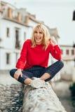 Menina loura de sorriso com camisa vermelha que aprecia a vida fora imagem de stock