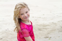 Menina loura de sorriso na praia no dia ensolarado Imagens de Stock