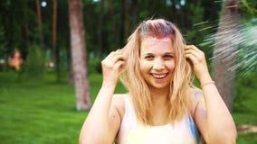 Menina loura de sorriso que está sendo polvilhada com o pó colorido no festival de Holi filme