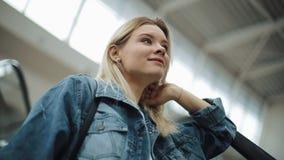 A menina loura de sorriso vai acima na escadaria movente em um shopping video estoque