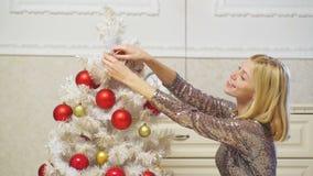 A menina loura decora uma árvore do White Christmas com as bolas vermelhas isoladas no branco Feliz Natal e ano novo feliz feriad video estoque