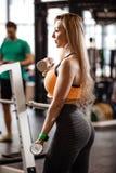 A menina loura delgada com o cabelo longo vestido em um sportswear est? fazendo exerc?cios com pesos no gym moderno com grande fotos de stock