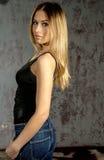 Menina loura delgada nova nas calças de brim e na camisa que levantam provocante Foto de Stock