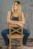 Menina loura delgada nova nas calças de brim e na camisa que levantam provocante Fotografia de Stock Royalty Free