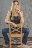 Menina loura delgada nova nas calças de brim e na camisa que levantam provocante Fotos de Stock
