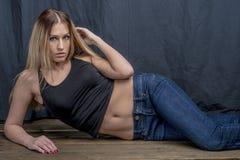 Menina loura delgada nova nas calças de brim e na camisa que levantam provocante Imagens de Stock