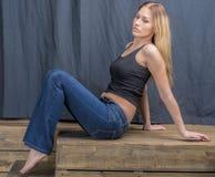 Menina loura delgada nova nas calças de brim e na camisa que levantam provocante Fotografia de Stock