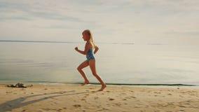 Menina loura despreocupada 5 anos de corridas ao longo da costa Ri fora de seus pés que voam muito espirro da água vídeos de arquivo