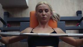 Menina loura do esporte atlético com o corpo perfeito da aptidão que faz o treinamento duro do exercício com a barra no banco do  video estoque