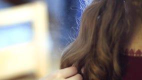 A menina loura do estilista faz o penteado a uma jovem mulher filme