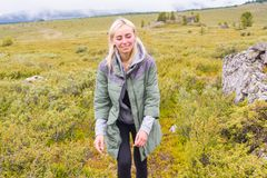A menina loura do turista em um revestimento verde que está em uma montanha fotografia de stock royalty free