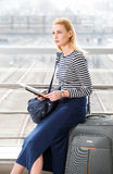 Menina loura do turista em uma camiseta listrada com uma trouxa que senta-se em uma mala de viagem na estação de trem e nas posse fotos de stock