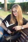Menina loura doce com os vidros que olham a você e que leem um livro em um banco de parque imagens de stock