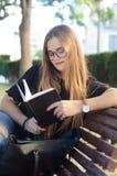 Menina loura doce com vidros que lê um livro em um banco de parque foto de stock royalty free