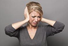 menina loura dos anos 20 na dor, sofrendo da dor de cabeça ou evitando o ruído Foto de Stock