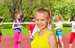 Menina loura e amigos que jogam o voleibol atrás Fotografia de Stock