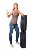 Menina loura e um par de pneumáticos para um carro No branco Imagens de Stock Royalty Free