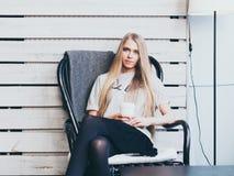 A menina loura elegante bonita com cabelo longo está descansando em um café com uma xícara de café que senta-se em uma cadeira Imagens de Stock
