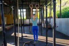 A menina loura em caneleiras azuis e em um t-shirt da parte traseira mantém h foto de stock