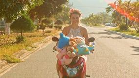 Menina loura em Garland Rides Scooter com os brinquedos ao longo da estrada filme