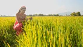 Menina loura em Garland Squats entre o campo verde do arroz vídeos de arquivo