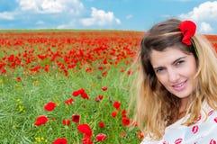Menina loura em um campo da papoila Fotografia de Stock Royalty Free