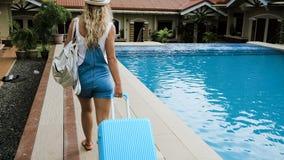 A menina loura em um chapéu e em macacões estabelece-se em um hotel tropical com um saco azul vídeos de arquivo