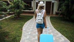 A menina loura em um chapéu e em macacões estabelece-se em um hotel tropical com um saco azul filme