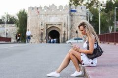 Menina loura em um vestido branco que senta-se em um passeio na ponte Imagem de Stock