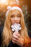 Menina loura encantador que veste o chapéu de Santa que morde a Fotografia de Stock