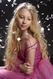 Menina loura encaracolado bonita da criança do adolescente que veste um Dr. cor-de-rosa do ar fotos de stock