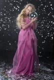 Menina loura encaracolado bonita da criança do adolescente que veste um Dr. cor-de-rosa do ar imagem de stock