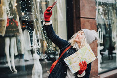 Menina loura encaracolado de sorriso com o mapa que faz o selfie, inverno Fotografia de Stock