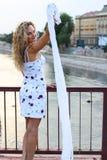 Menina loura encaracolado que está na ponte e que acena com um branco Imagens de Stock Royalty Free