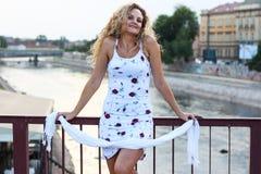 Menina loura encaracolado que está na ponte e que guarda as escumalhas brancas Fotos de Stock Royalty Free