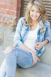 Menina loura engraçada bonita com bordos grandes com as calças de brim do sorriso, vestir e uma camisa branca encantadores andand Fotografia de Stock Royalty Free