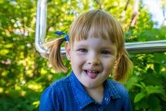 Menina loura engraçada no parque Criança fêmea bonita pequena que anda em um dia ensolarado do verão foto de stock royalty free