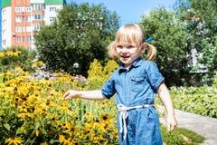 Menina loura engraçada no parque Criança fêmea bonita pequena que anda em um dia ensolarado do verão imagem de stock royalty free