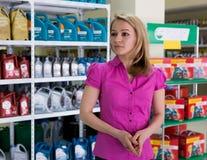 A menina loura escolhe o óleo de motor na loja das peças de automóvel Fotografia de Stock
