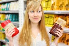 A menina loura escolhe o arroz na loja Fotografia de Stock