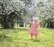 Menina loura feliz da criança que tem a dança do divertimento no parque fotografia de stock