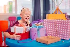 Menina loura feliz que senta-se na tabela com presentes fotos de stock royalty free