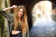 Menina loura feliz que sorri no fundo urbano Fotos de Stock Royalty Free
