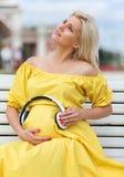 A menina loura grávida inclina fones de ouvido para inchar-se Imagem de Stock Royalty Free